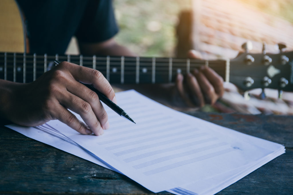Songwriter holding guitar and pen learning how to write song lyrics