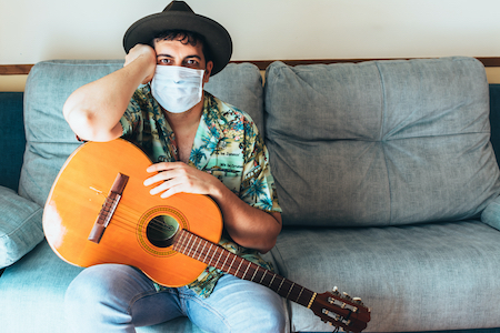 Masked man with guitar on couch