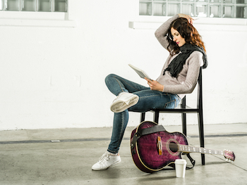 Girl writing songs with guitar on floor