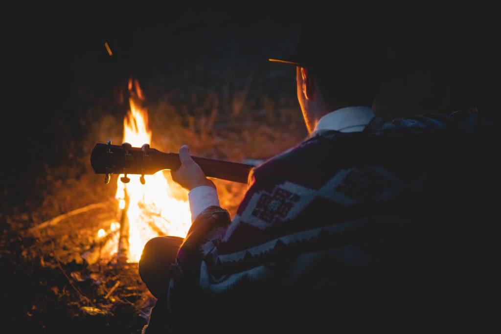 Man playing guitar at camp fire
